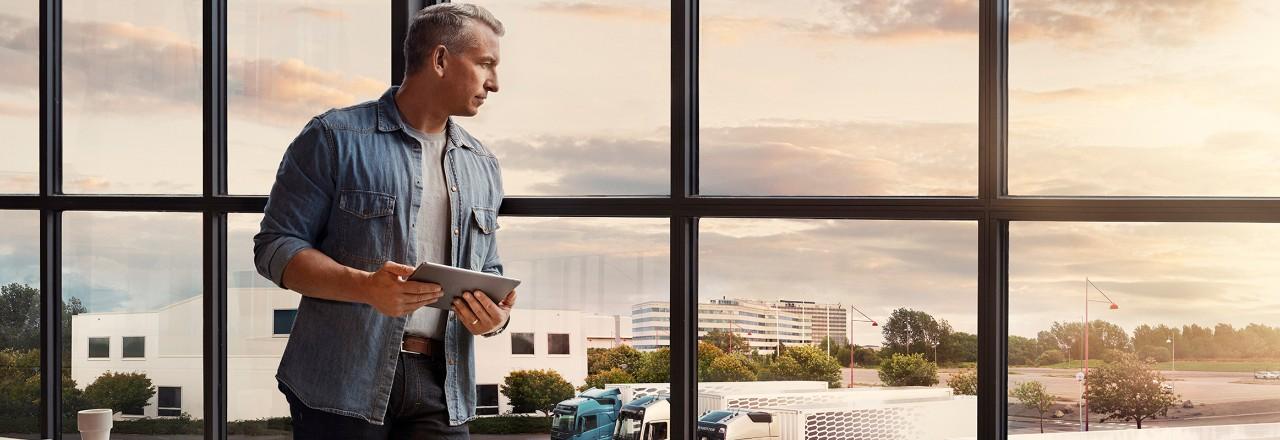 Човек кој држи таблет стои покрај прозорецот и гледа надолу кон возниот парк од камиони